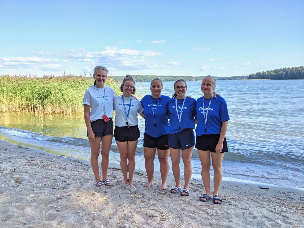 Fem unga kvinnor klädda i Folkhälsan-skjortor står och håller om varandra på en strand.