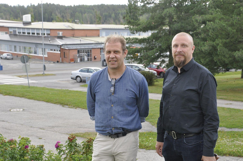 Två män med en skola i avlägsen bakgrund.