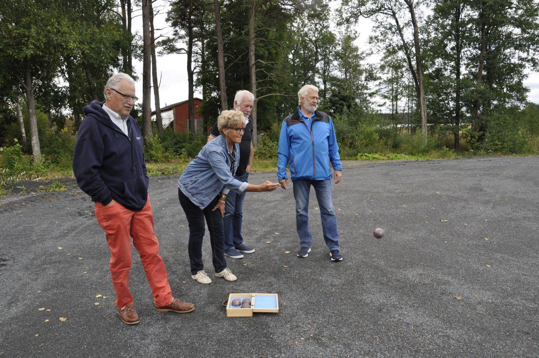 Fyra äldre personer spelar boule på en stor plan. Damen kastar sin kula.