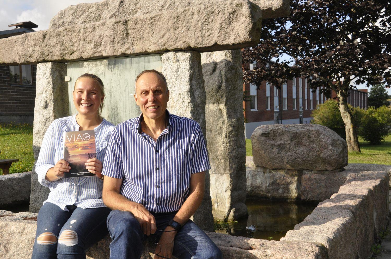 en kvinna och en man sitter vid ett monument i sten . Har en broschyr i handen.