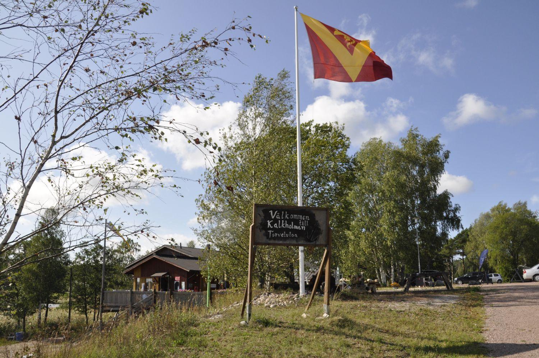 naturfint landskap med en byaflagga och en skylt: Välkommen till Kalkholmen.