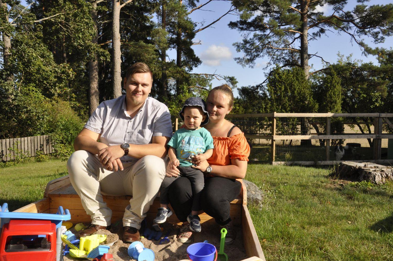 Familj sitter på kanten till en sandlåda