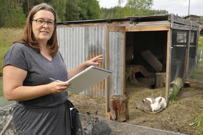 Kvinna står med block och penna vid kanininhägnad.