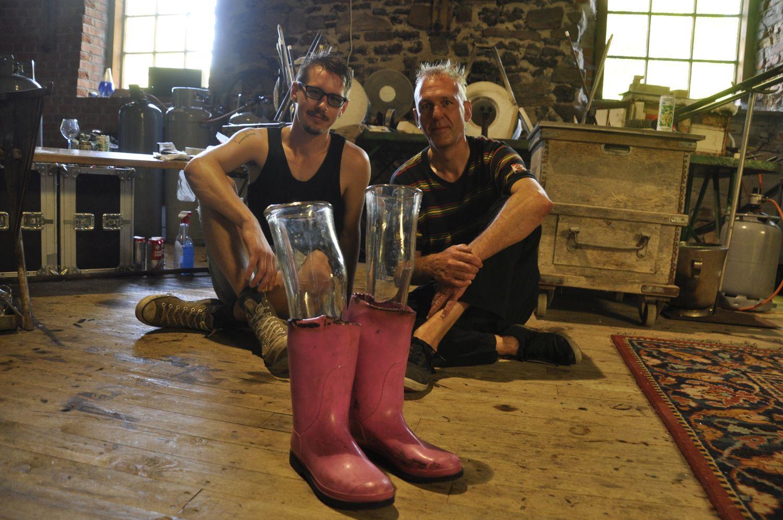 Rosa gummistövlar med glasben i. Bakom sitter två män på golvet i glasblåsarverkstaden.