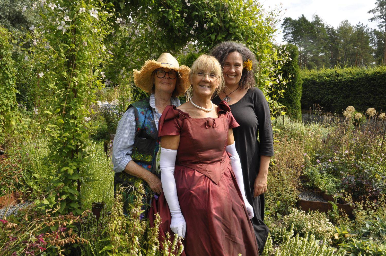 Tre glada damer i sina rolldräkter i en trädgård.