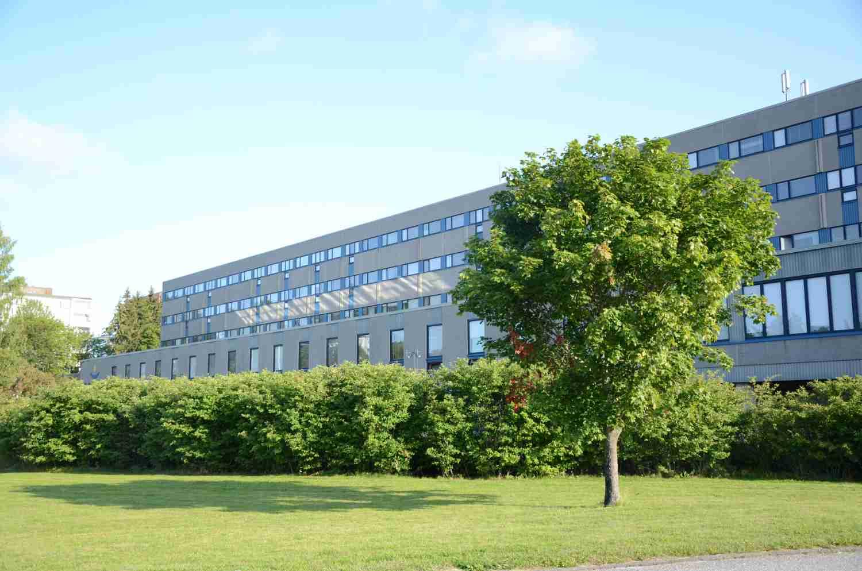 En stor byggnad med grönskande träd i förgrunden.
