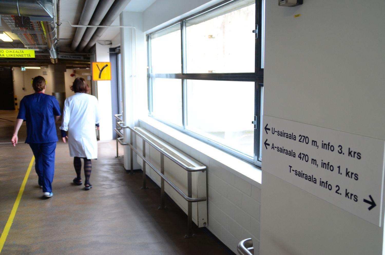 En tunnel där två sjuksköterskor går. På bilden syns också en skylt som pekar ut åt vilket håll och hur många meter man ska gå för att komma till A-, T- och U-sjukhusen.