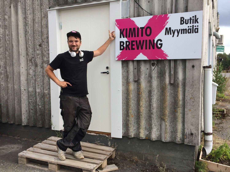 """Ung man i arbetskläder står utanför en industrihall. På väggen en stor skylt: """"Kimito Brewing""""."""