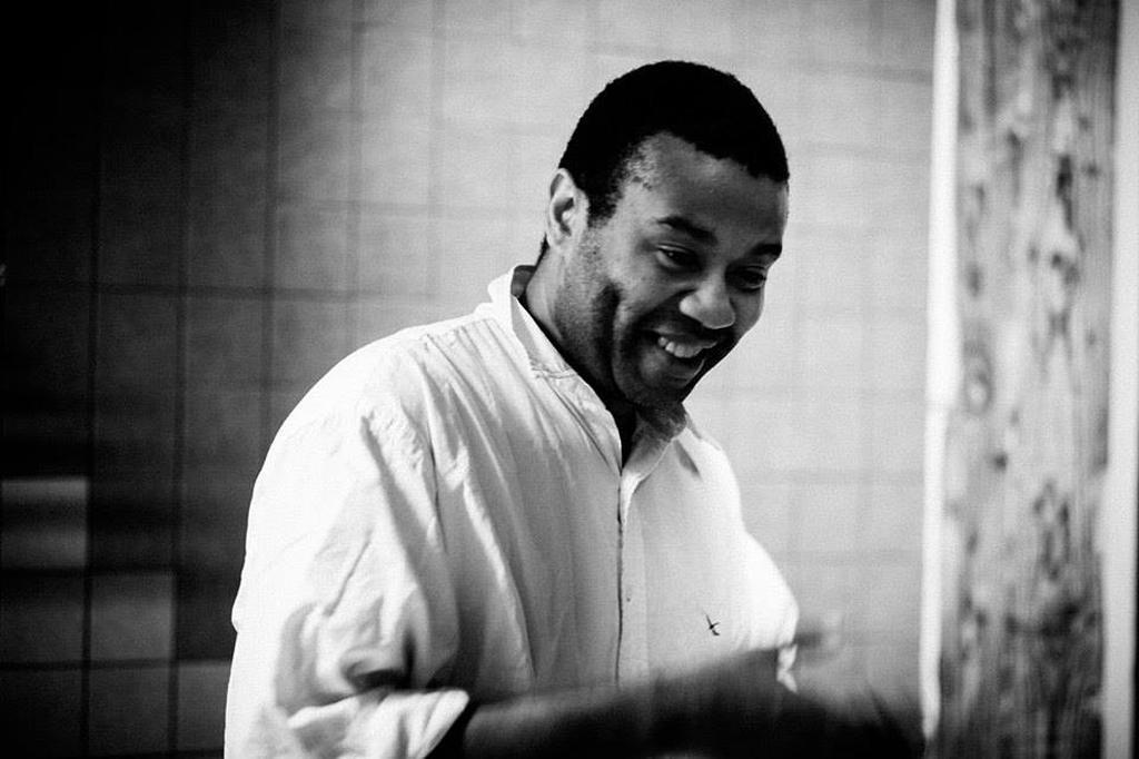 En svartvit bild av en man som ler.
