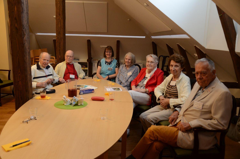 En grupp seniorer samt gruppledaren sitter kring ett bord och ler mot kameran.
