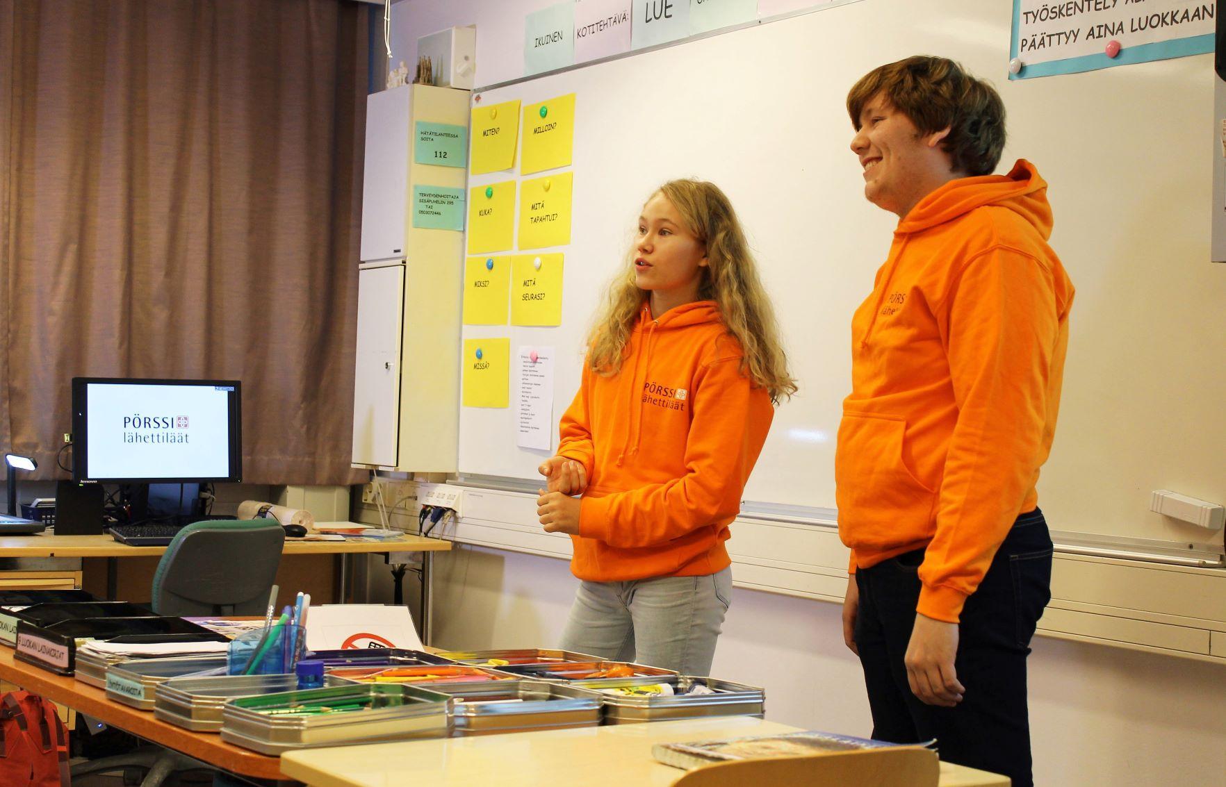 Två unga i orangea collegar står framme i klassen