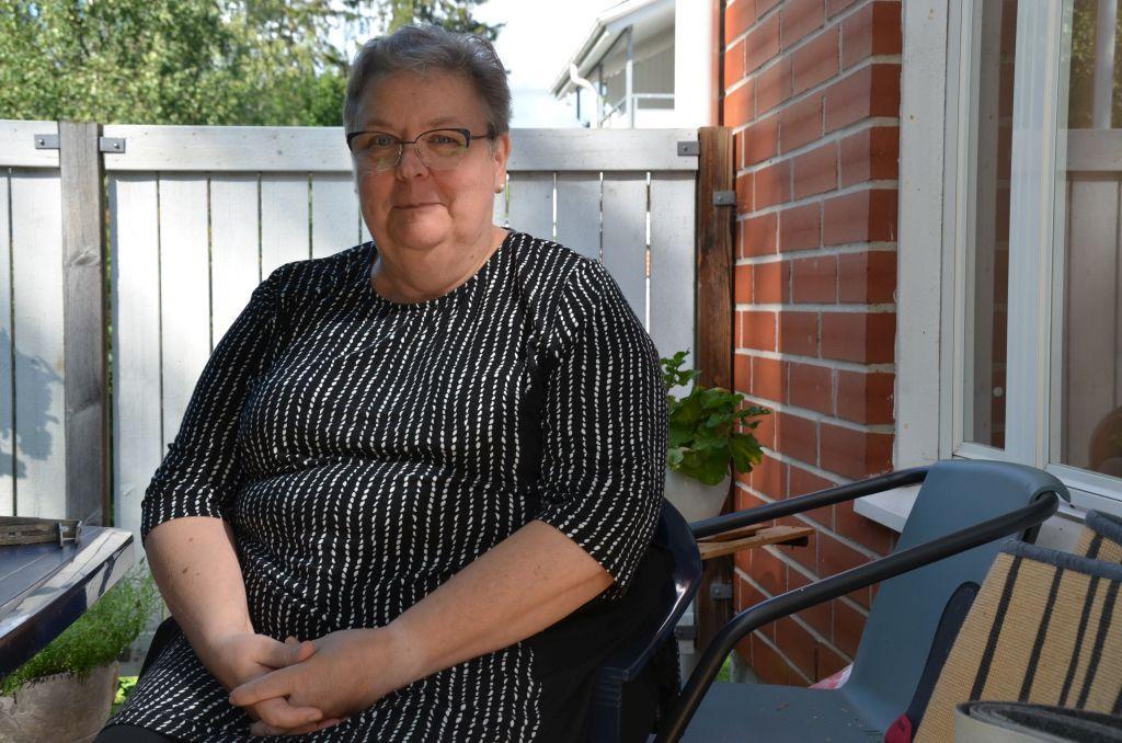 En kvinna sitter i en stol på en bakgård och ser in i kameran.