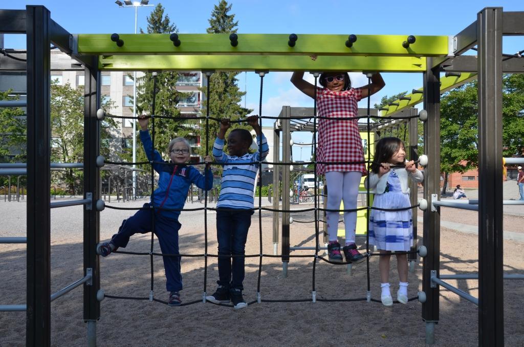 Fyra barn hänger i en klätterställning.