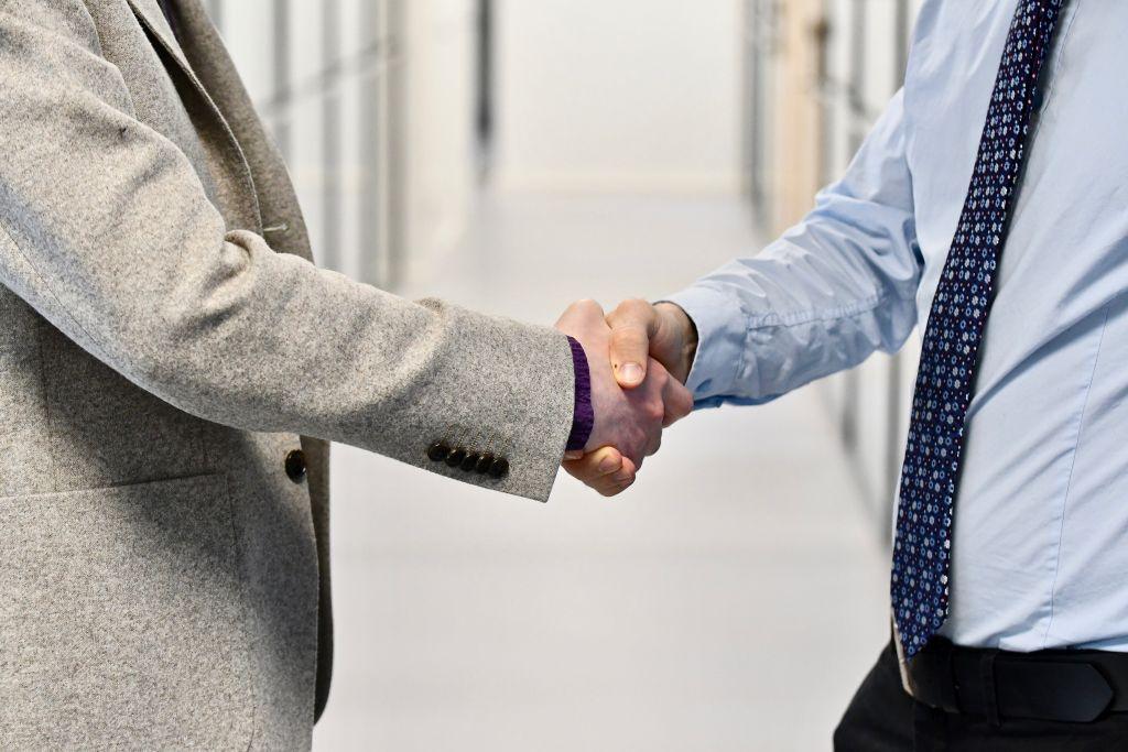 Två välklädda män som skakar hand.