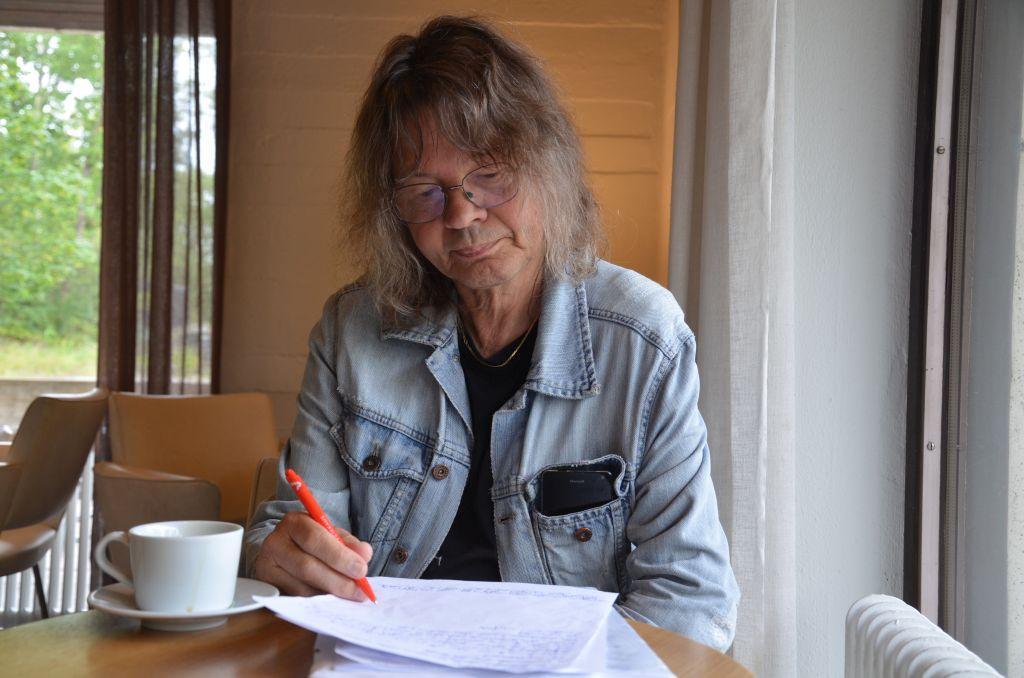 En långhårig man i jeansrock sitter på ett kafé och skriver. Framför sig har han et papper med anteckningar och ett kopp kaffe.