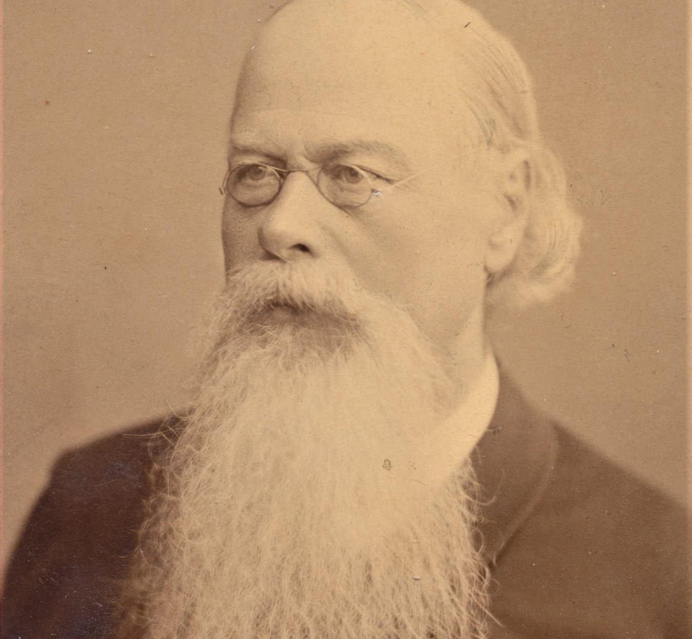 Gammalt fotografi som föreställer en man med långt skägg och glasögon.