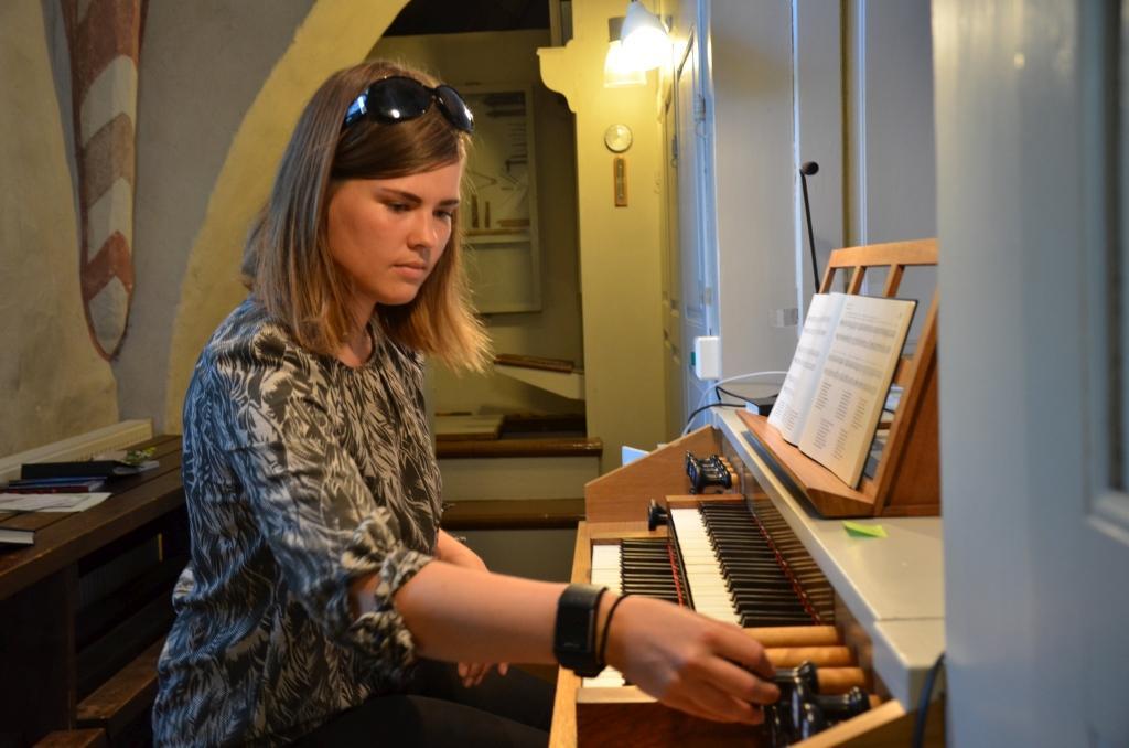 En kvinna sitter och spelar på en orgel.