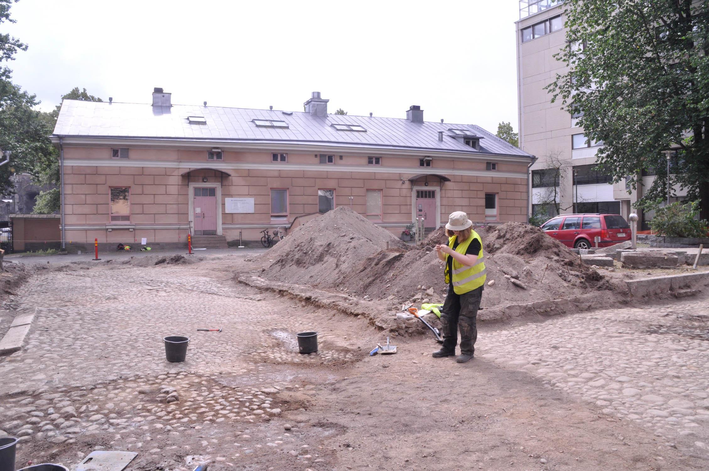 Gårdsplanen på Slottsgatan 24 grävs upp. Nu har man kommit fram till gatubeläggningen från 1800-talet. Arkeolog Hanna-Maria Pellinen inspekterar ett fynd.
