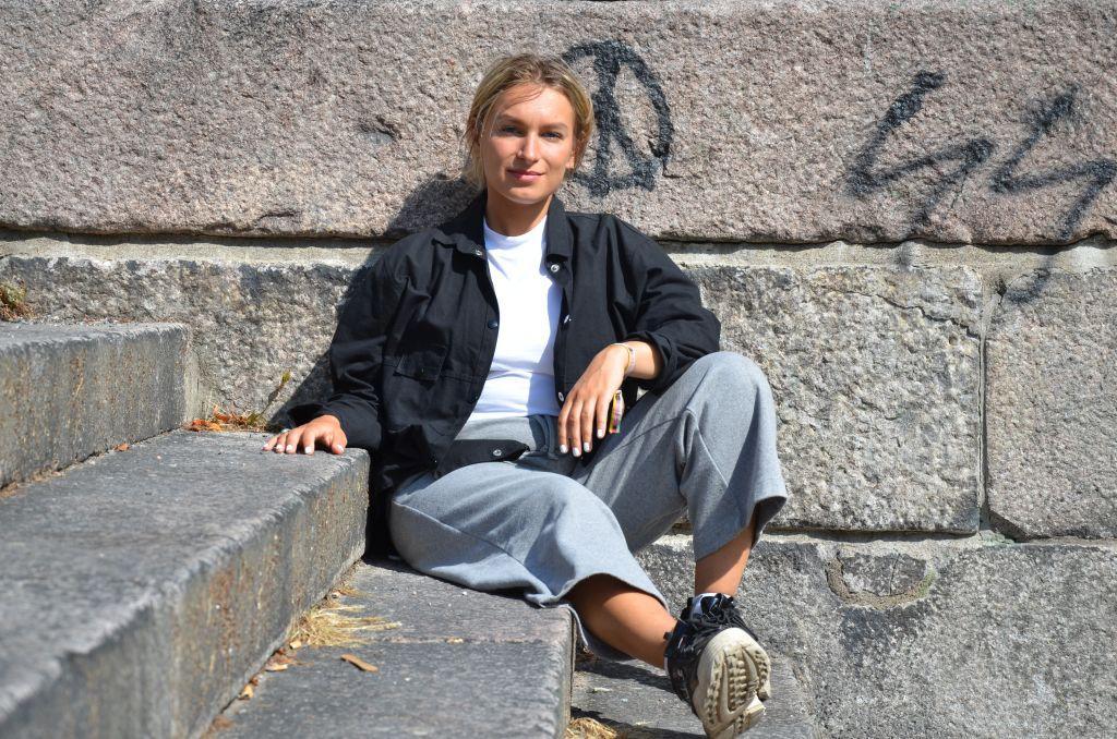 En ung kvinna sitter i en stentrappa och lutar sig mot en stenvägg som är täckt av med grafitti.