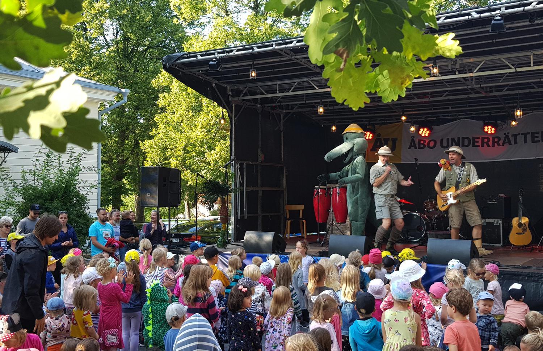 Utomhusscen med massor av barn i publiken
