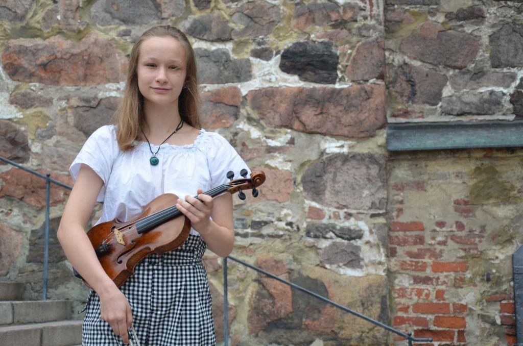 En ung flicka håller i en fiol framför domkyrkan i Åbo.
