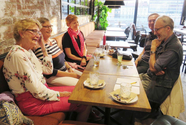 Fem glada människor vid ett kafébord