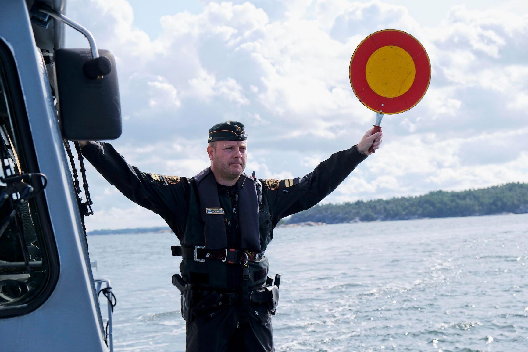 Sjöbevakare håller upp en stoppskylt