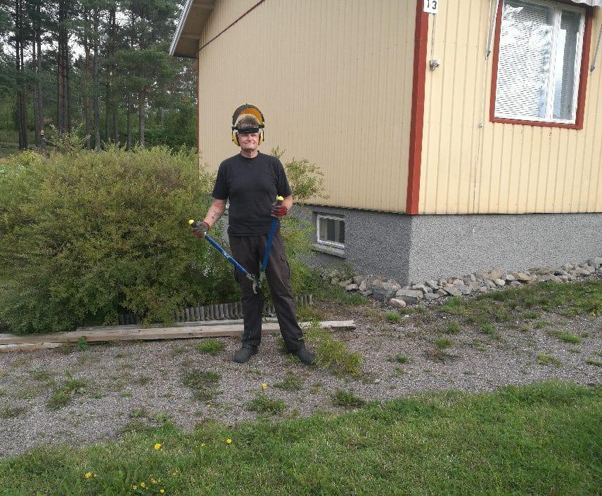 Man står vid ett hus med arbetsutrusning för trädgårdsarbete.