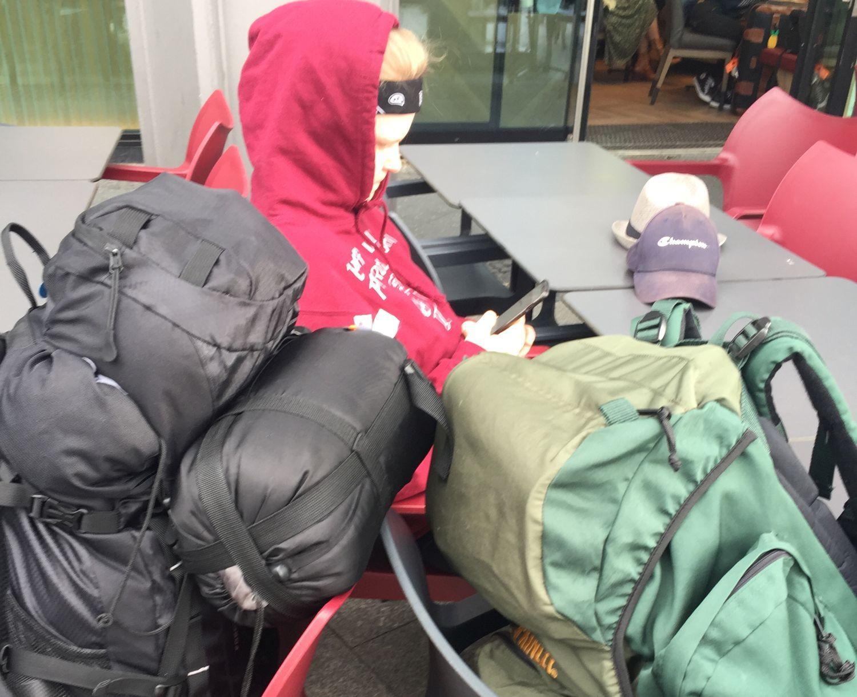 Stora ryggsäckar och en tonåring som läser på sin mobil