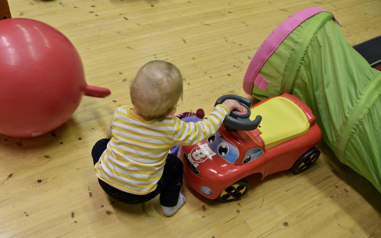 Ett litet barn leker med en leksaksbil.