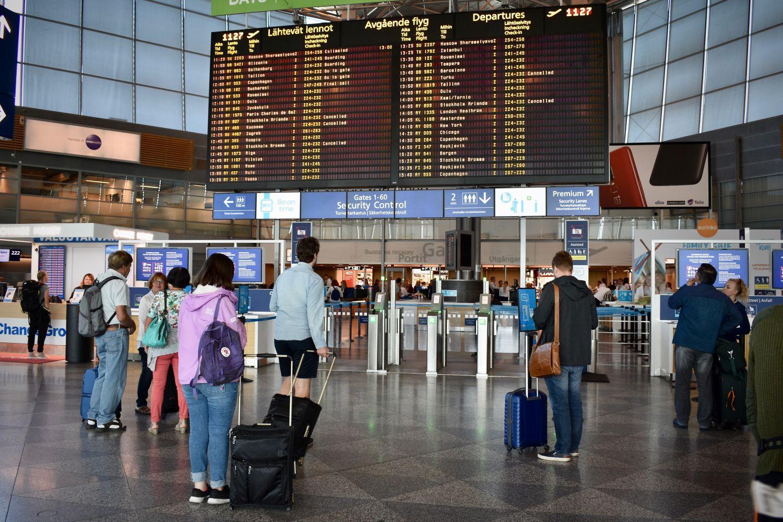 Människor som står framför en skärm med uppgifter om flygtider på en flygplats.