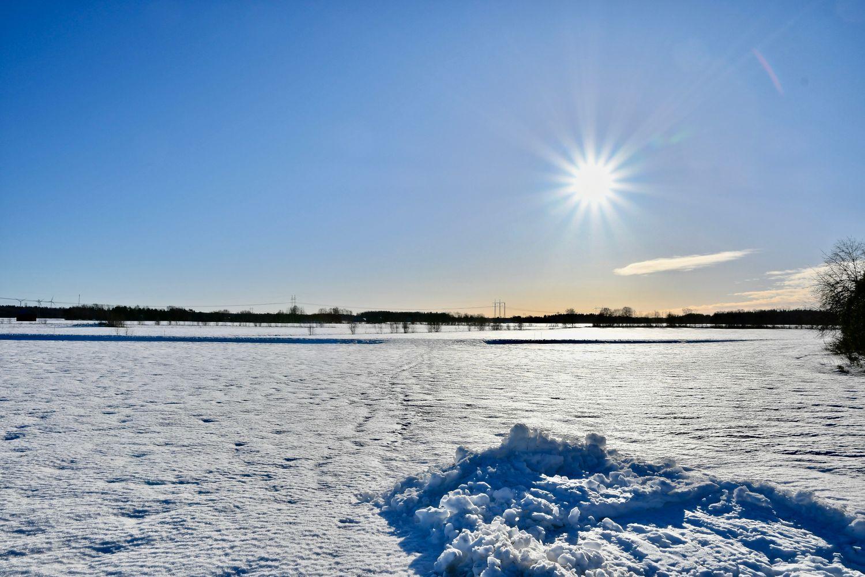 Snöigt landskap med sol.