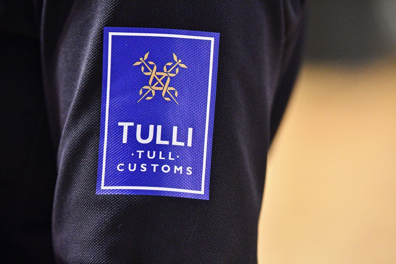 Närbild på en tulltjänstemans jacka med emblem.