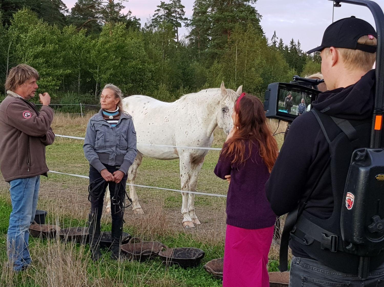 Ett filmteam bakifrån. Framför deras kamera syns en programledare, samt de två intervjuade framför en hästhage och en vit häst.