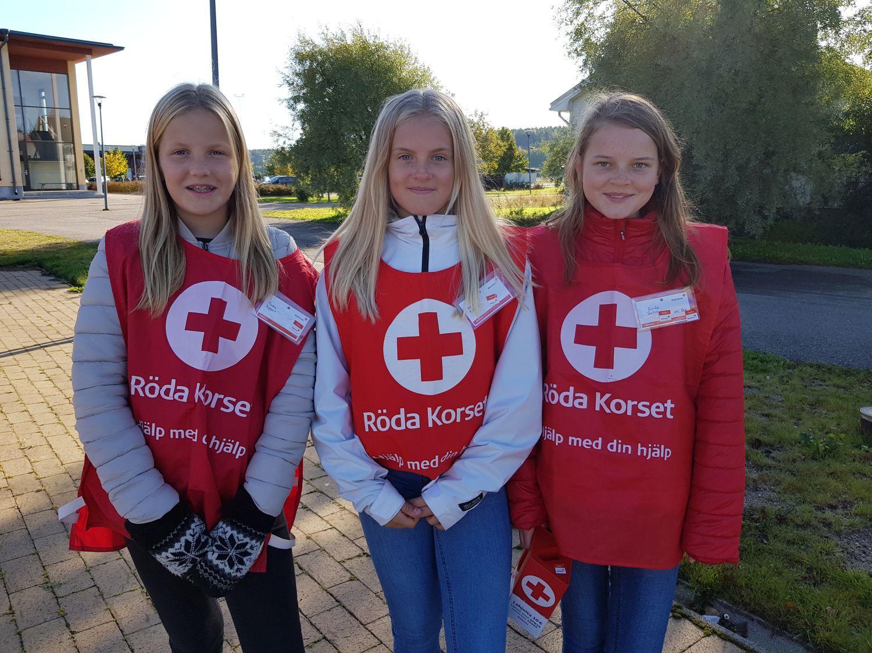 tre flickor iklädda FRK-västar och med en insamlingsbössa.