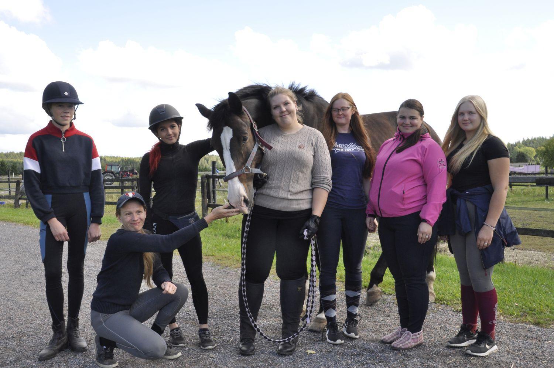 En grupp studerande tillsammans med en häst.