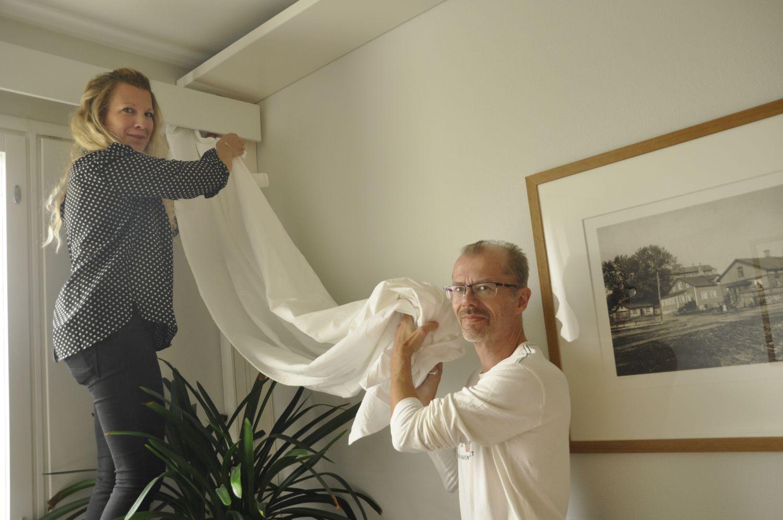 Två personer hänger upp gardiner