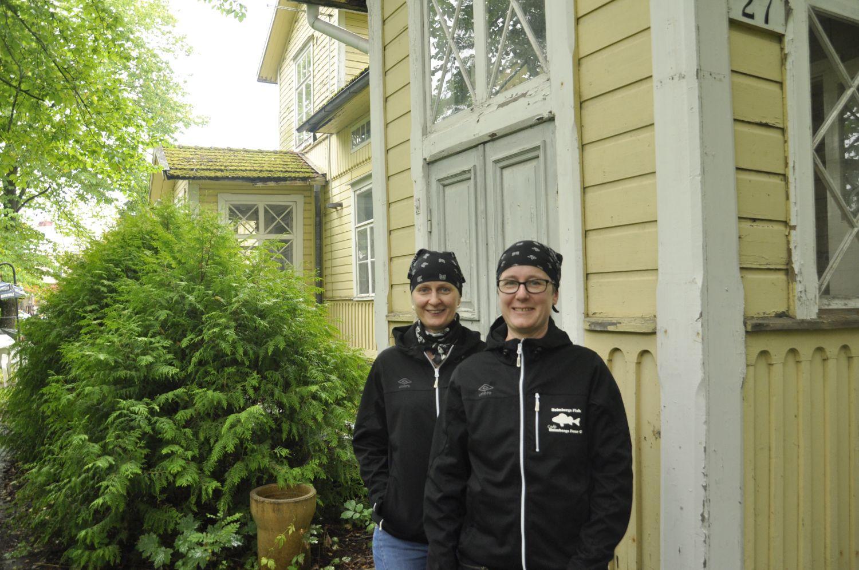 Två damer bredvid ett gammalt gulr trähus