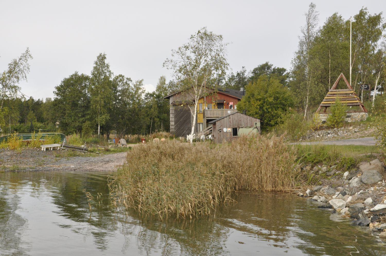 Från havet syns en liten båtupptagningsplats och en byggnad.