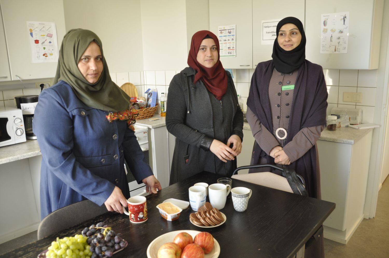 Tre syriska kvinnor i ett kök, där de plockar fram kaffe med tilltugg.