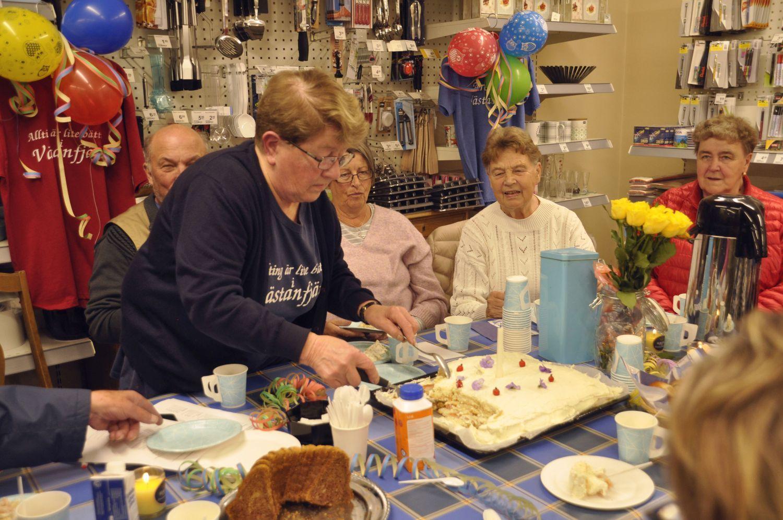 Kaffekalas pågår, folk sitter kring bordet . En dam står och serverar tårta.