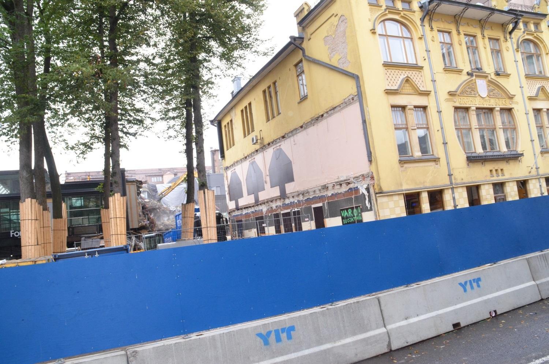 Det gula Hamburger Börs-huset i Åbo centrum, med en grävmaskin i bakgrunden.