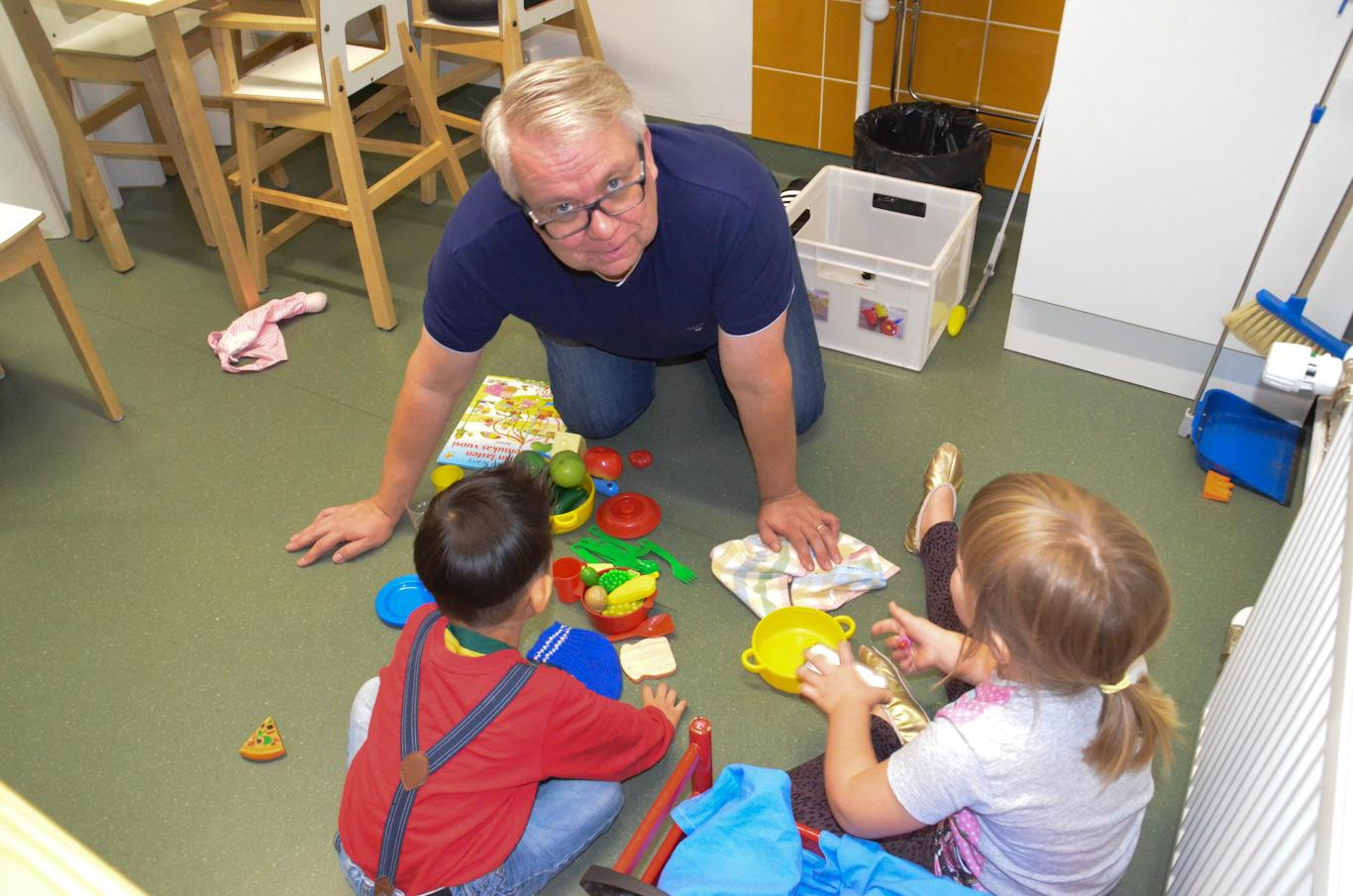 Medelålders man leker med ett par barn på golvet.