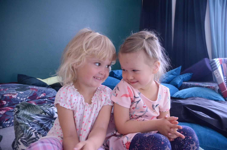 Två flickor som ser förtroligt på varandra.