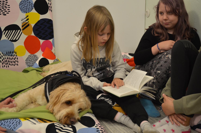 två flickor läser för en hund
