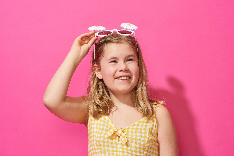 Flicka fotad mot pink bakgrund