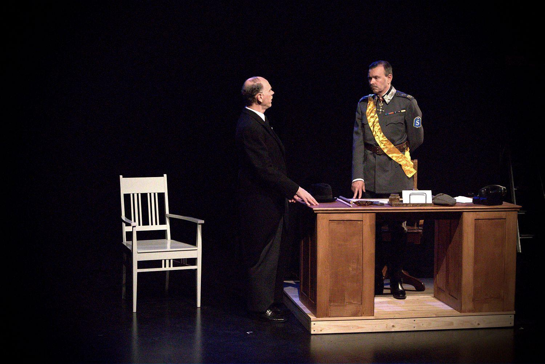 En mörklagd teaterscen med marskalk Mannerheim bakom ett skrivbord, med en gäst iklädd jackett med ryggen mot kameran.
