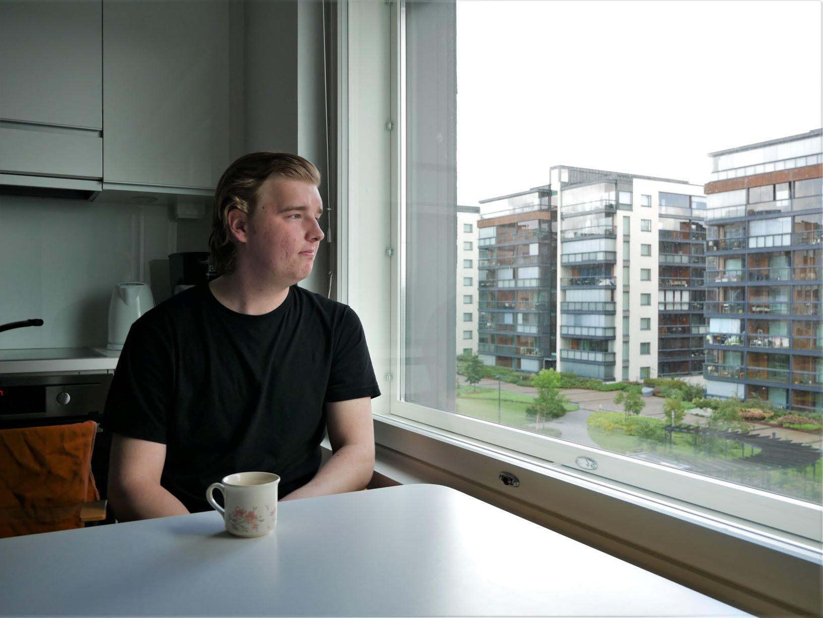 EN ung man sitter vid köksbordet och tittar ut genom fönstret. Det syns höghus i bakgrunden