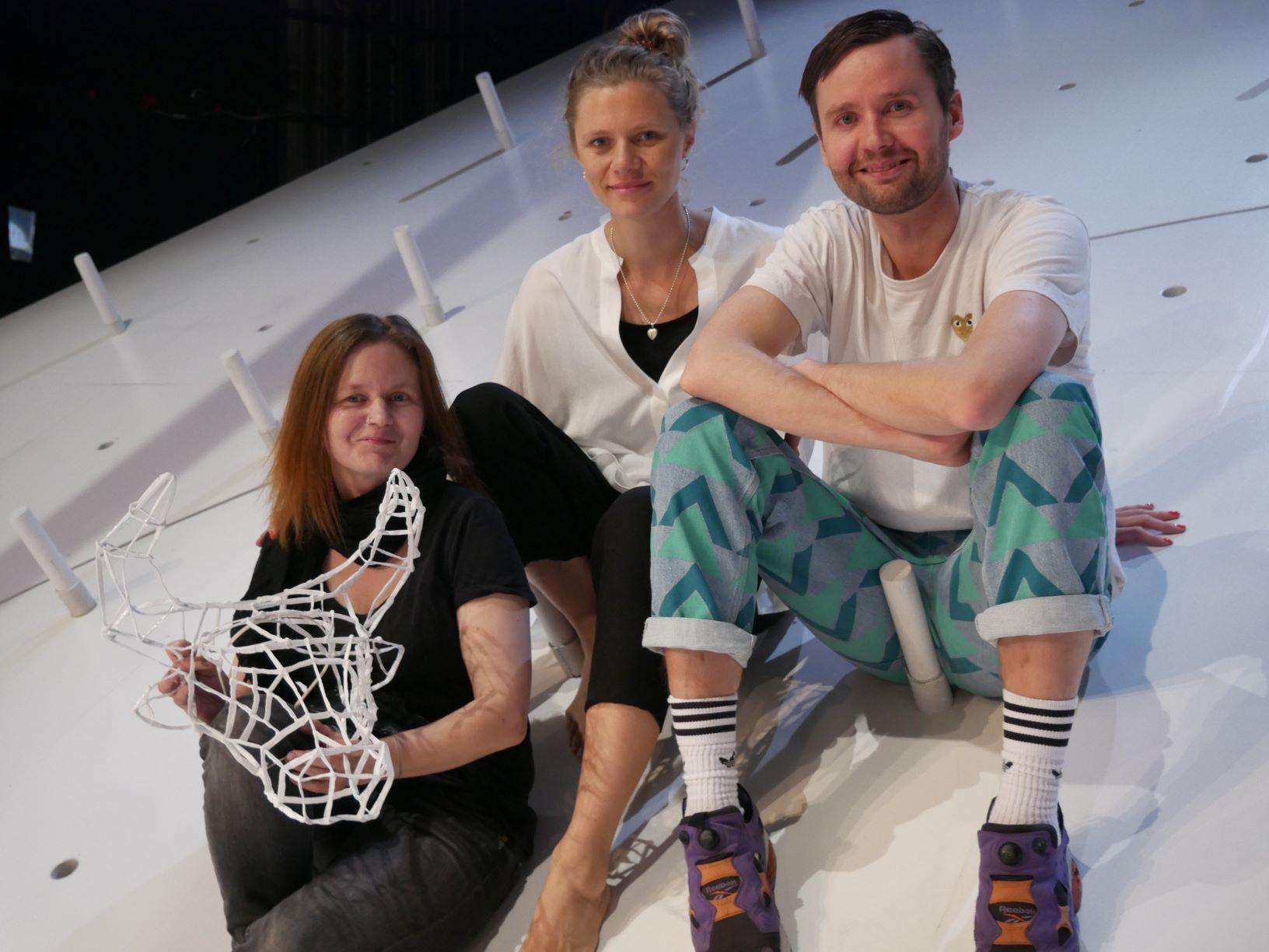 Tre personer sitter på scenen