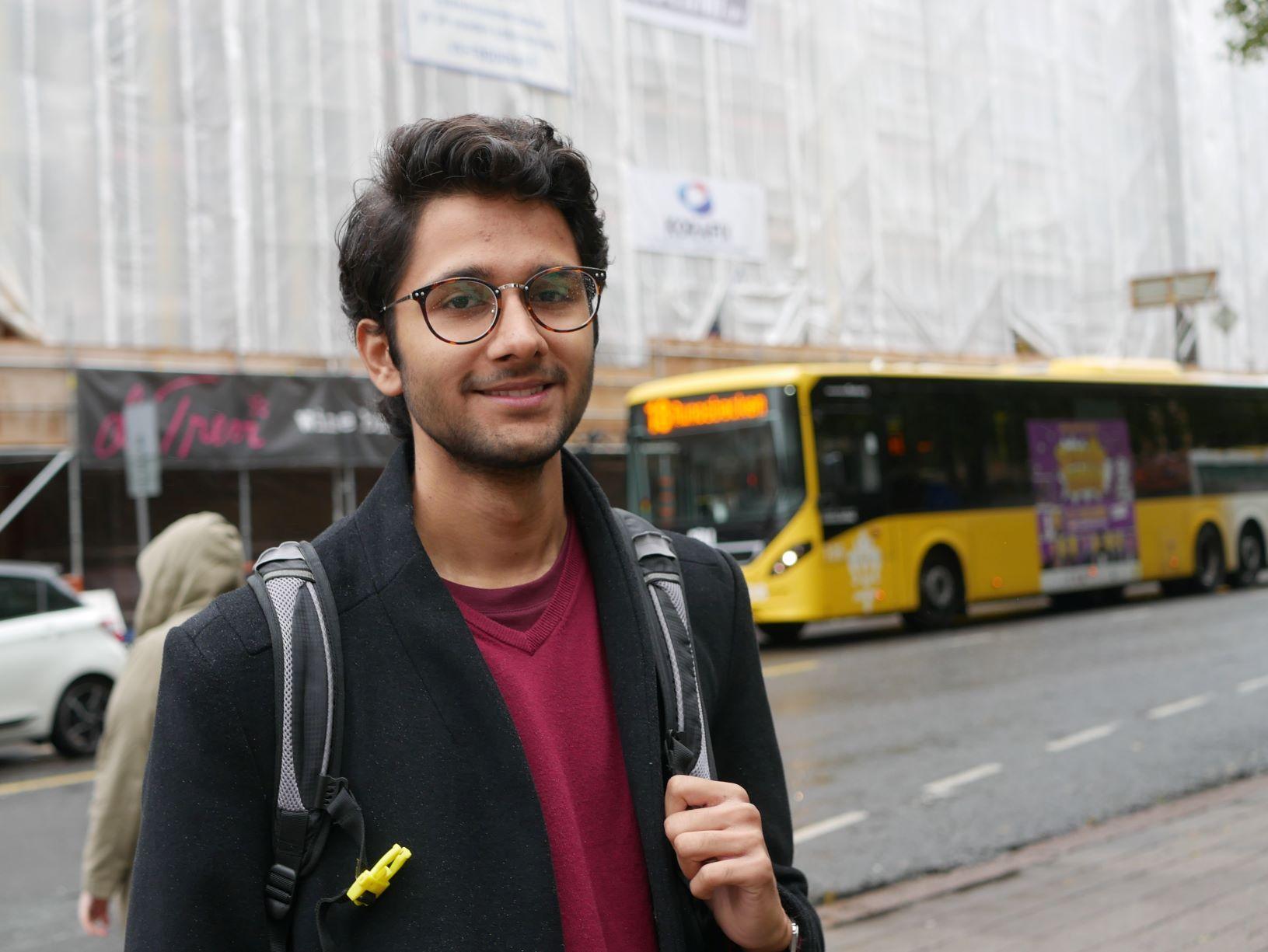 En man står vid vägen med buss i bakgrunden